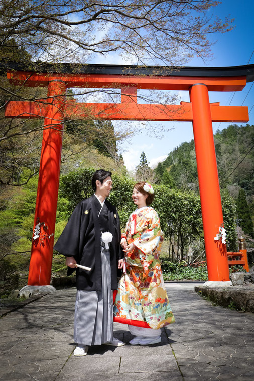 Couple wearing kimono in front of a Torii gate in Kyoto