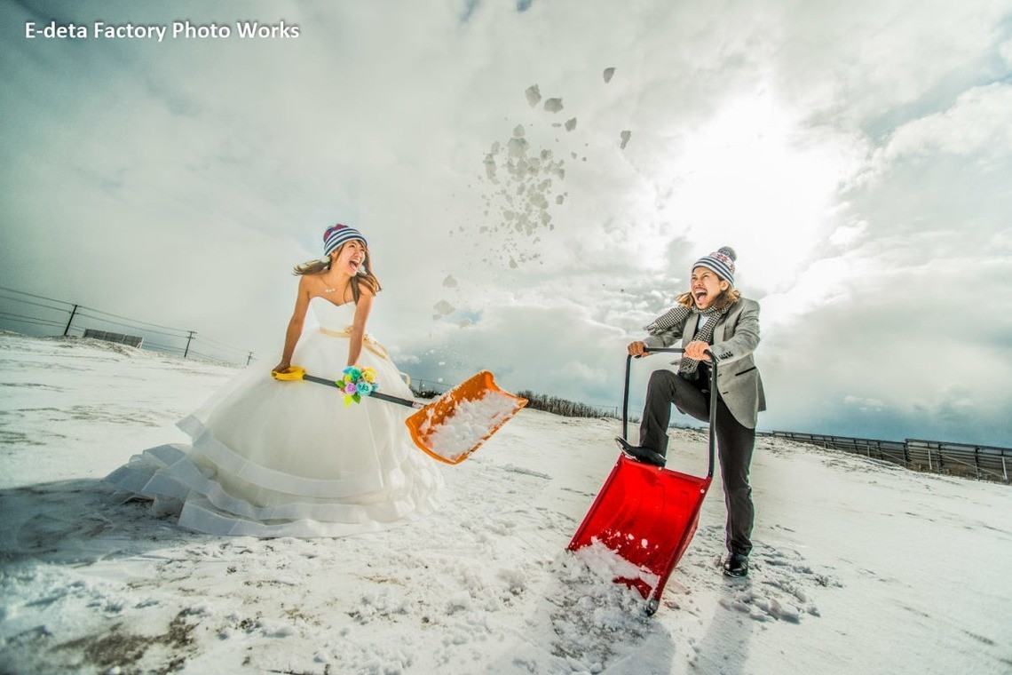 Couple in wedding attire showing snow together in a field. Photo by E-Deta Factory