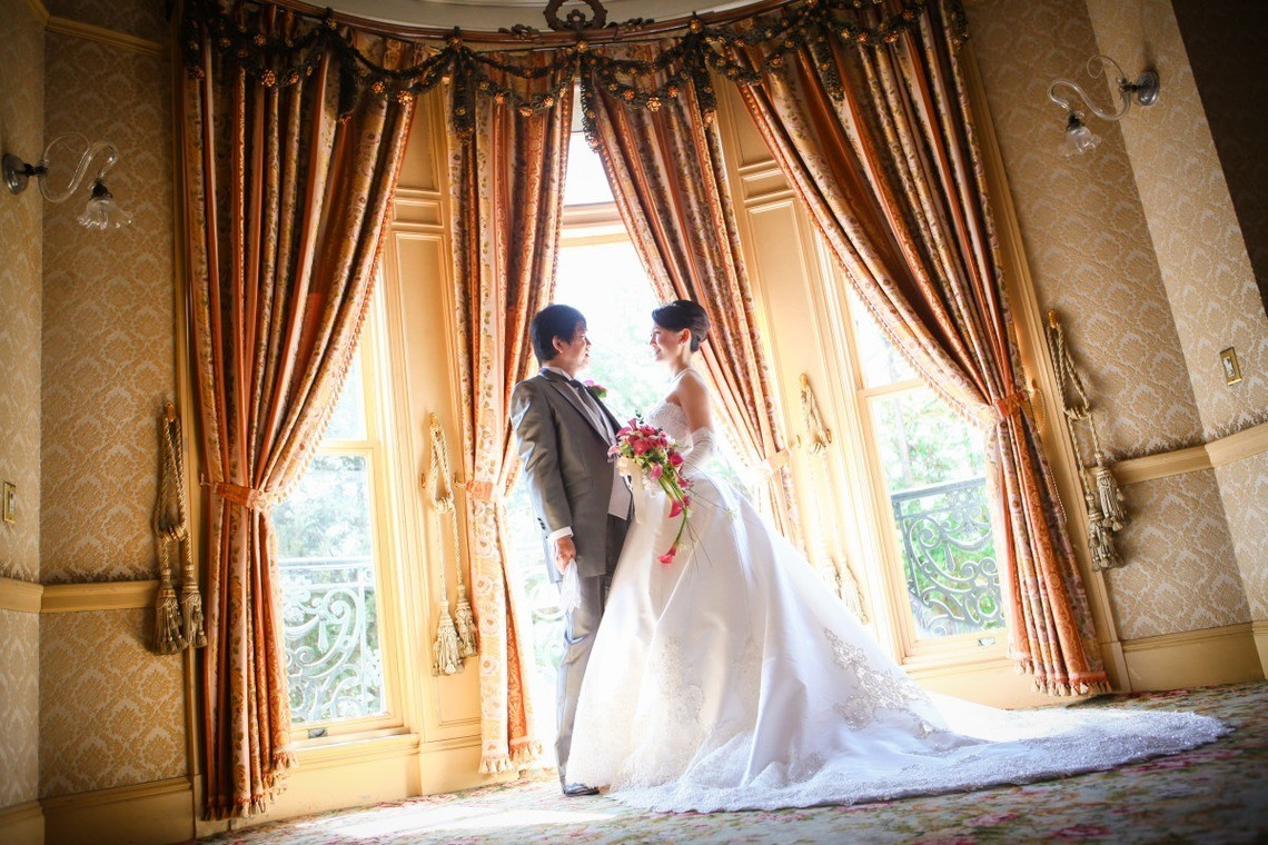 Couple in wedding clothes posing in elegant grand room. Taken by Murata Photo Works.