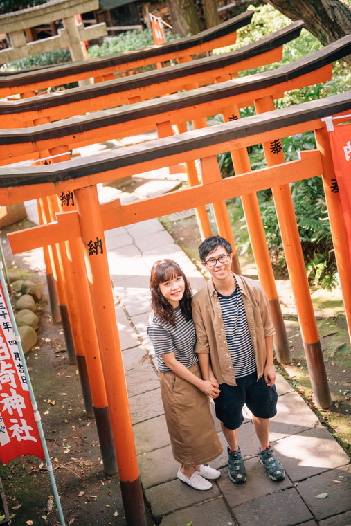 Couple in casual-wear posing with multiple Torii