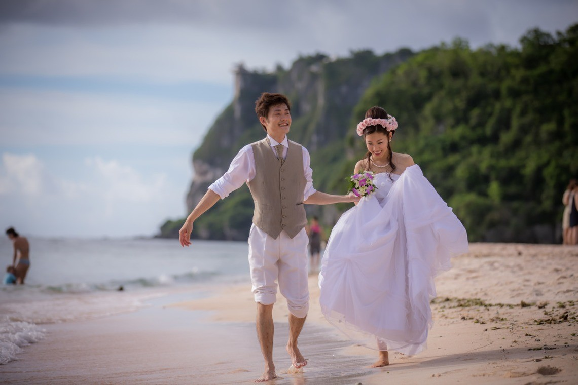 Couple in wedding dress walking down a beach barefoot. Taken by Yuki Ogawa