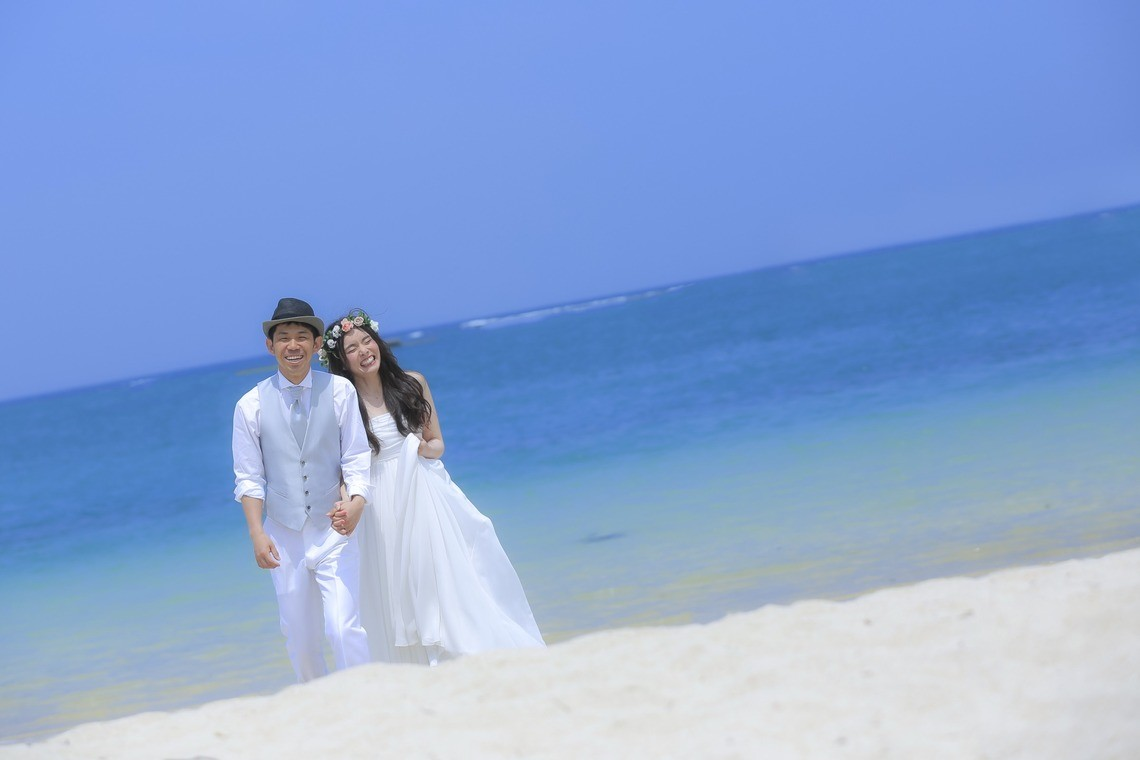A couple posing with the blue oceans of okinawa