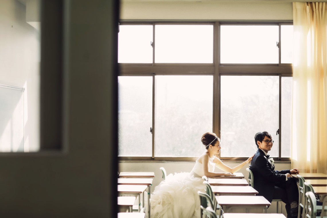 Bride and Groom in their wedding clothes sitting in the classroom they met in. Taken by Elle Pupa