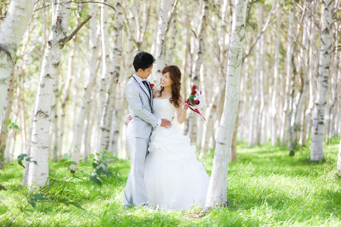 Couple in wedding dress posing in a woods like a fairytale.