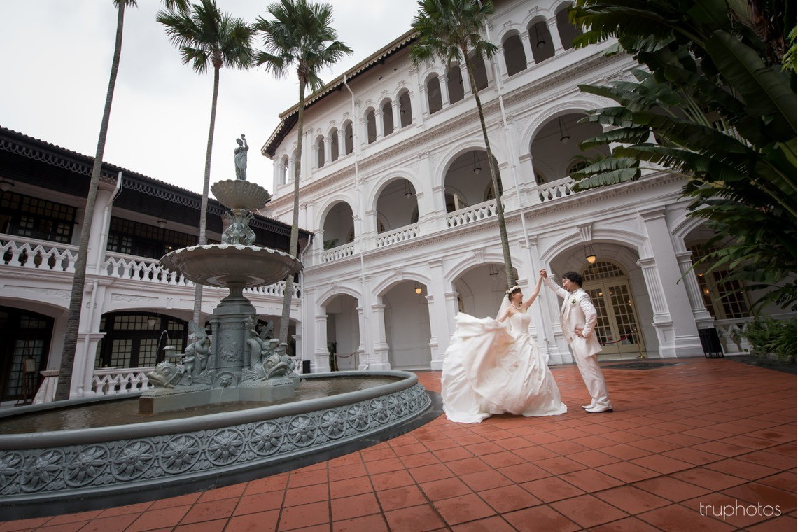 Matching white dress and tuxedo with western architecture. Photo by Truphotos