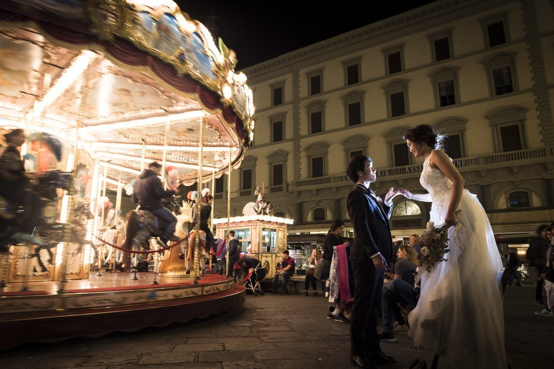 Wedding couple next to a carousel in Italy — Photo by Ruu Photographer