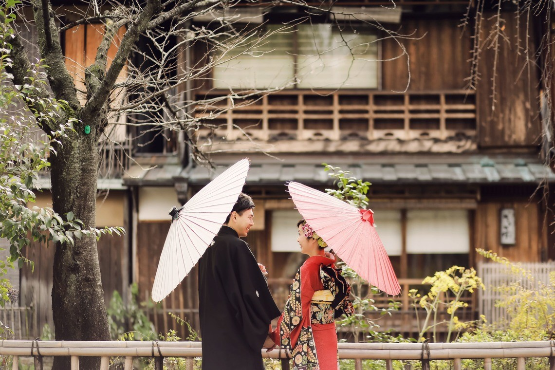 A couple in kimono holding traditional umbrellas in front of a japanese building