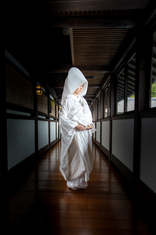 Lady in Shiromuku in the hallway of a wooden Japanese house