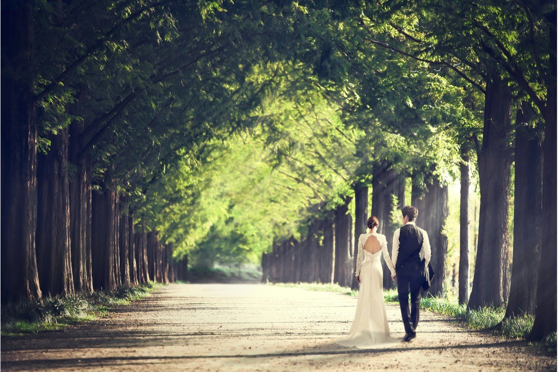 Wedding dress and tuxedo couple walking down mysterious beautiful tree path. Taken by Studio Howl