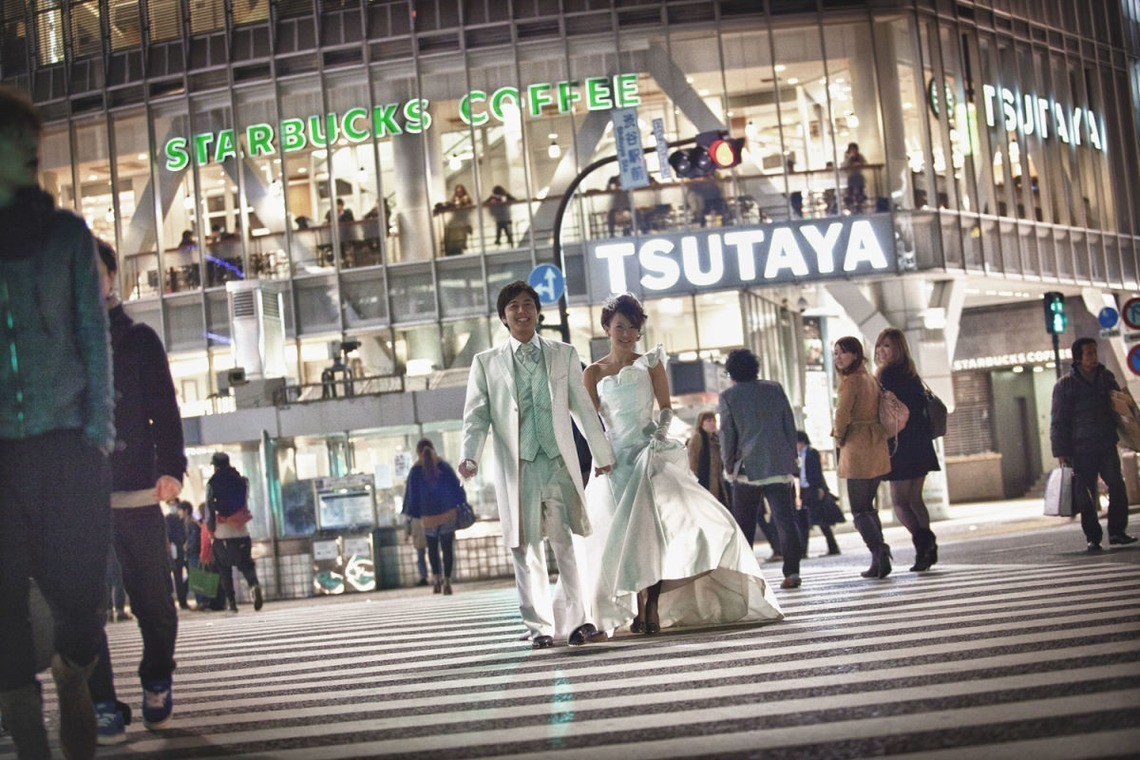 Bride and groom in matching white wedding attire at Shibuya Crossing by Photo by An'Z Photo
