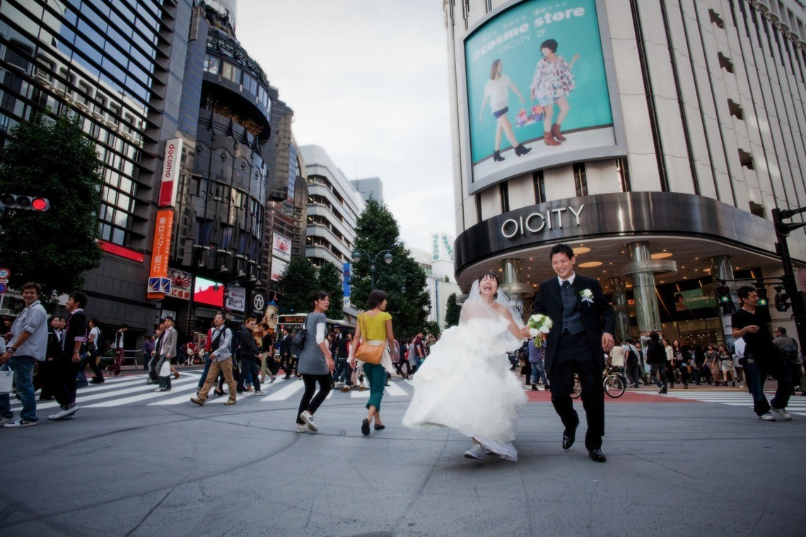 A couple running in the streets in their wedding attire. Taken by Yuki Ogawa