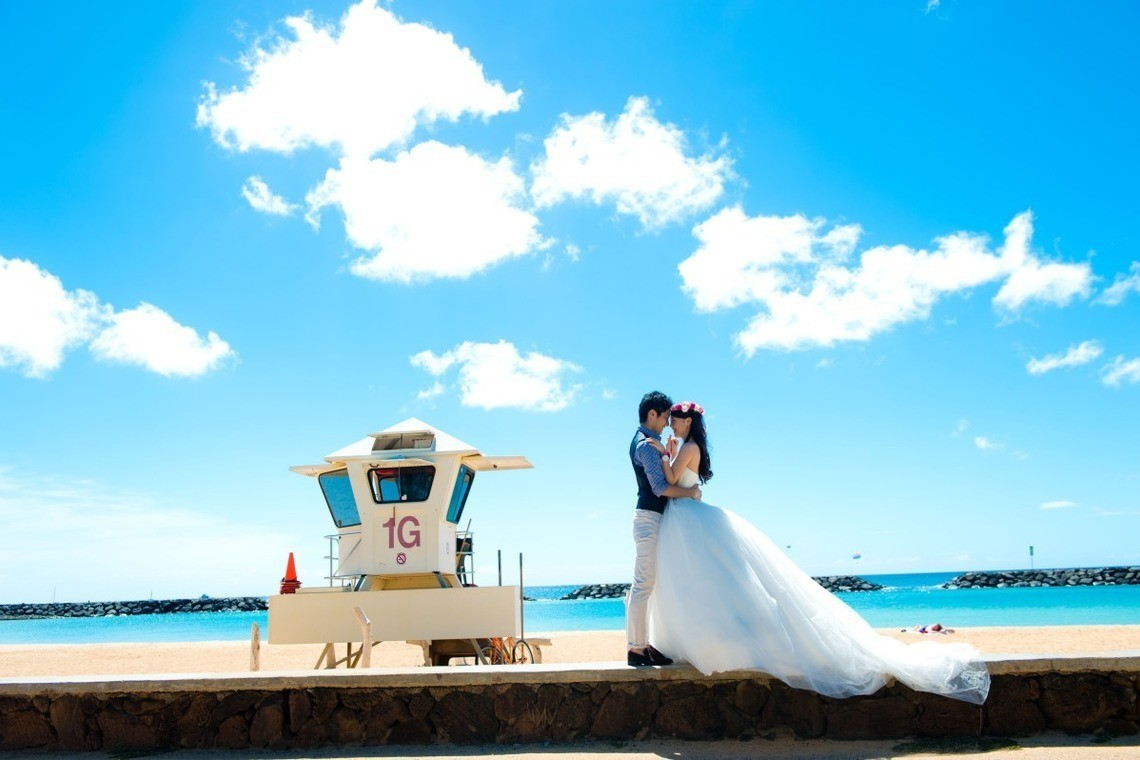 A beautiful couple together under a blue sky. Photo by Jason Tanega Photography