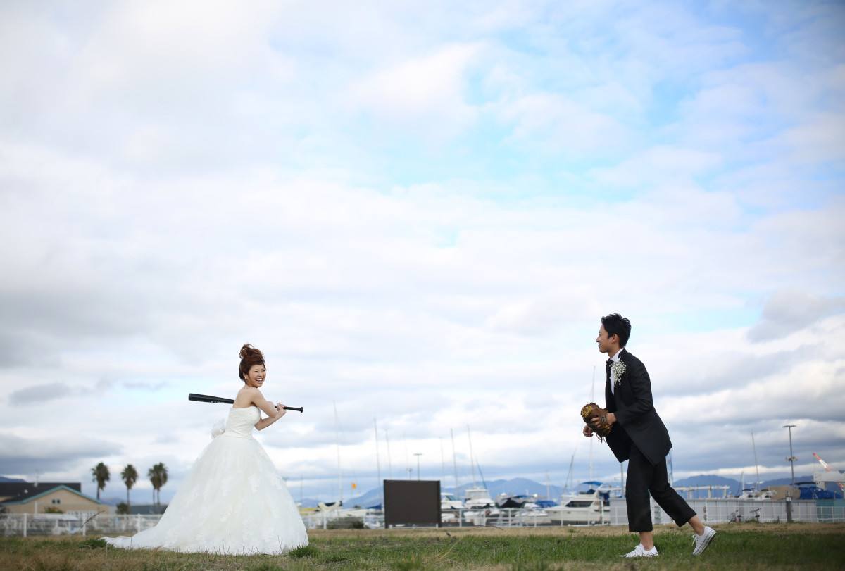 Couple playing baseball in their wedding attire. Taken by Studio Lucuss