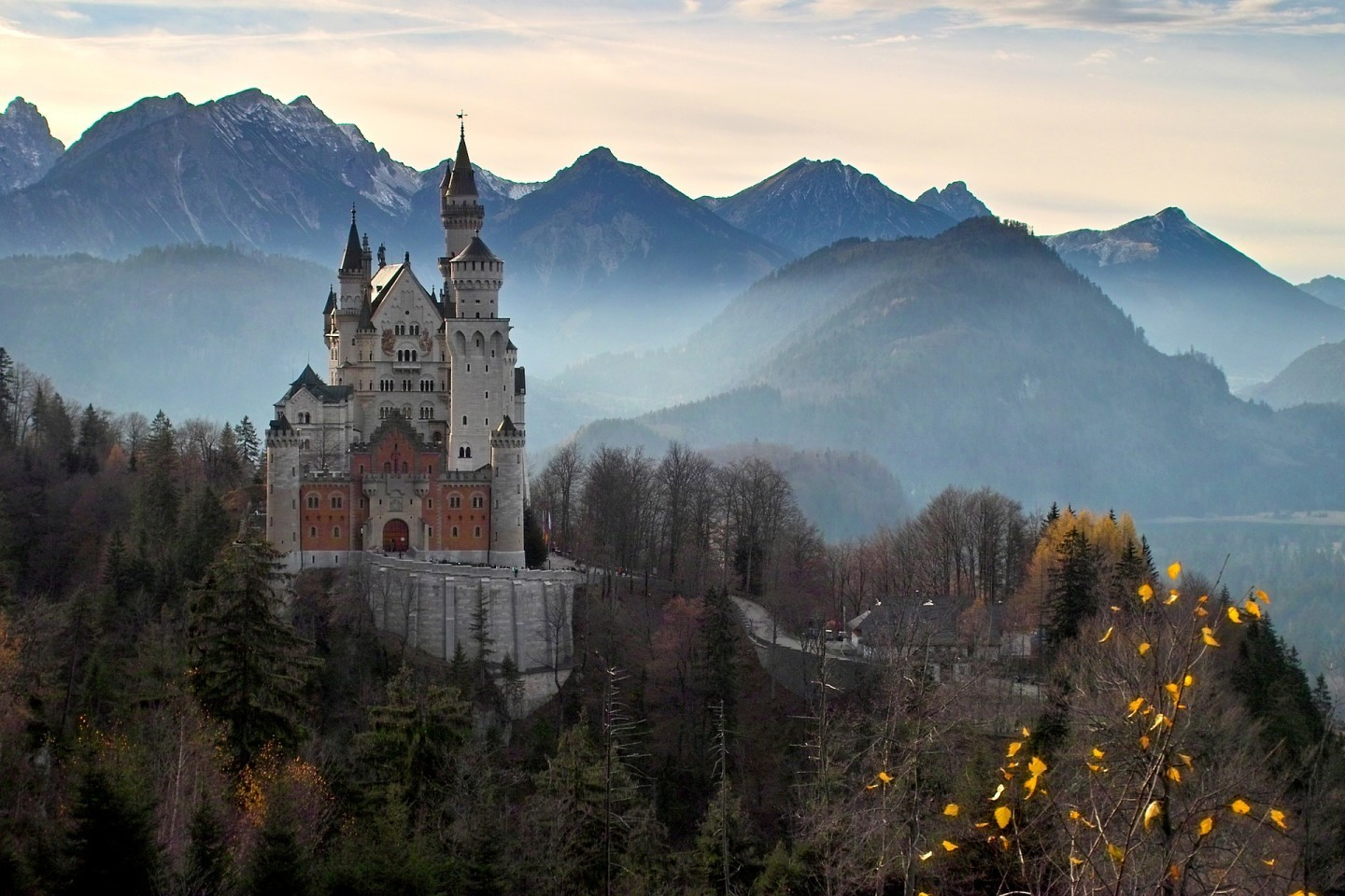 King Louis II Bavaria Castle with mountains and forest in the background