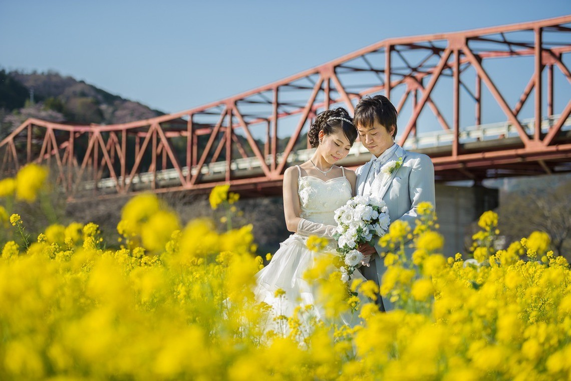 Couple in wedding dress and tuxedo, posing with a field of flowers in front of a bridge. Taken by Photoimagic.