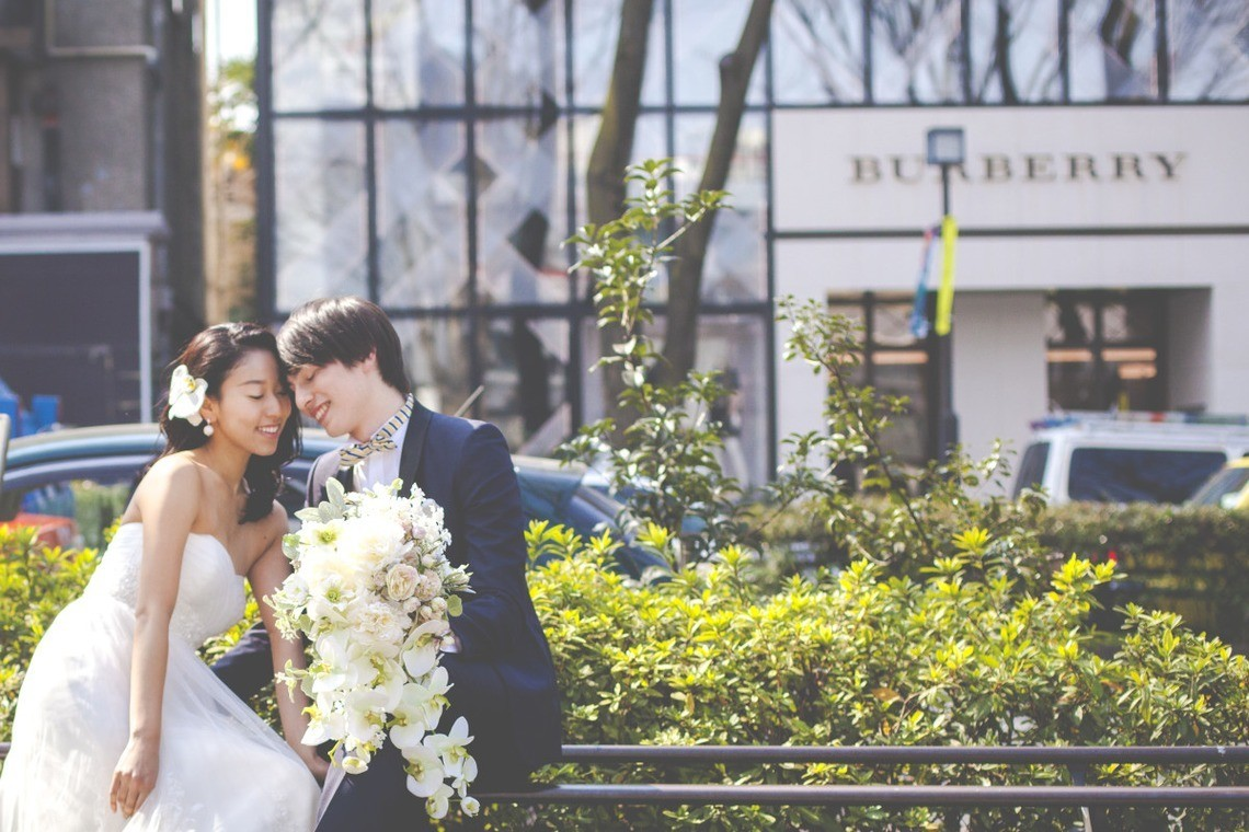 Bridal dress and tuxedo with white bouquet, posing in Omotesando. Photo by banana monkey pictures.