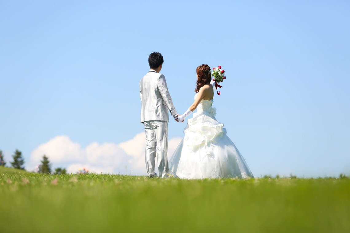 A couple in bridal dress stare up at the sky together in the fields.