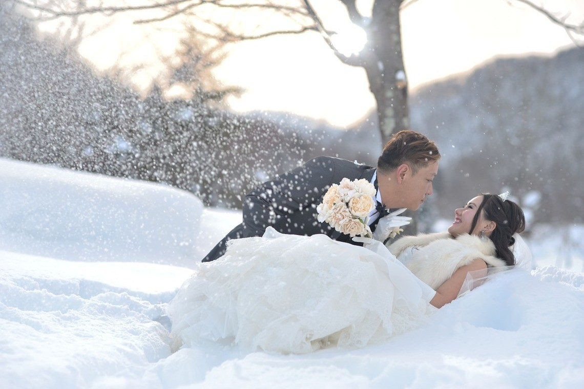 Wedding couple in bridal clothes poses in the snowy field