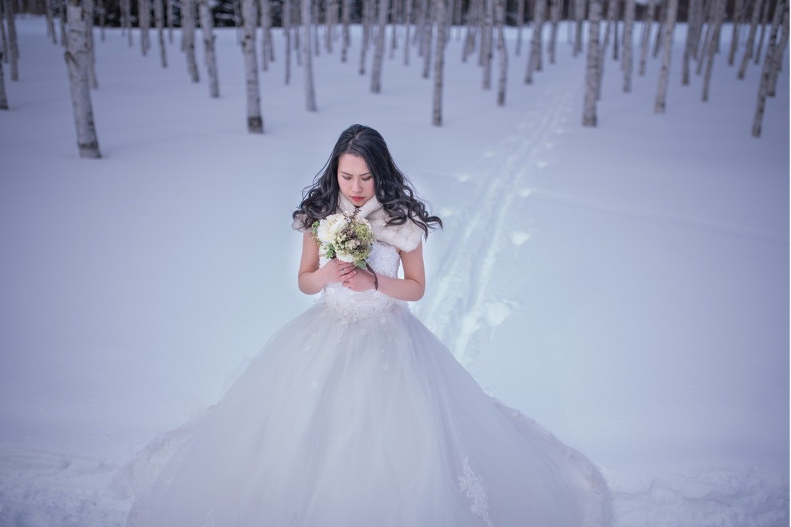 Bride walking through snowy woods.