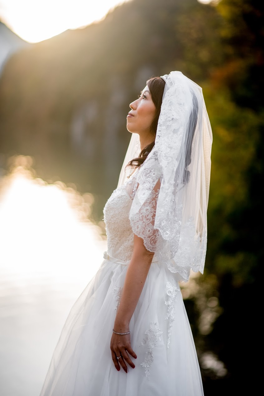 Lake Photo in Wedding Dress, posing elegantly by looking up toward the sky