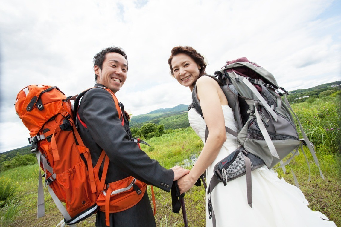Backpackers. The bride is in her wedding dress with her backpack in a field with the groom. Photo by Panda Studio Japan